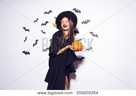Halloween Witch with a carved Pumpkin and dark glasses  Beautiful young surprised woman in witches hat and costume holding pumpkin. Wide Halloween party art design