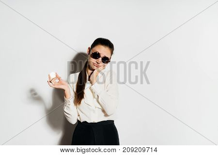 A beautiful girl in a blouse and black round glasses is holding a gold coin in her hands. Isolated on white background. Bitcoins, crypto currency, electronic money.