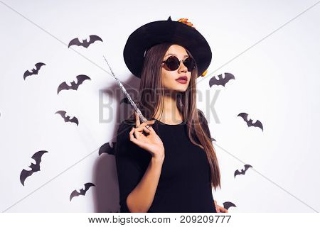 The Halloween witch in a big black hat and glasses with a magic wand in his hand looks away. The girl was going to a Halloween party