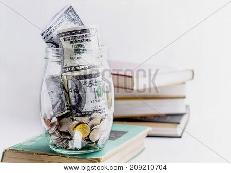 Coins and banknote in a glass jar on the textbook.The concept of business growth financial or money savings