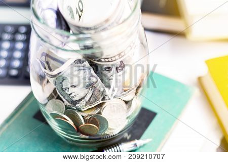 Coins pen and banknote in a glass jar on the textbook.The concept of business growth financial or money savings