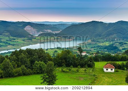 A small white house with a brown roof on the background of the coastal valley of the lake with large hills in cloudy weather. Rovni lake, Valjevo, Serbia.