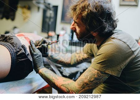 Professional artist making tattoo in salon. Making tattoo on the leg