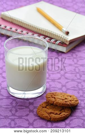Milk and cookies for an after school snack. In vertical format and shot in natural light.