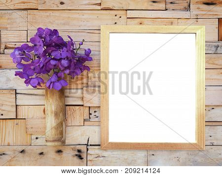 Violet vanda orchid in bamboo vase and blank picture frame hanging on wooden plank wall. Shabby vintage interior style.