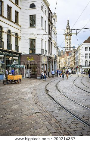 GHENT BELGIUM - JUNE 22 2016: One of the roads in Ghent with curves tram rails restaurants and the Post Plaza Clock Tower in the background in a cloudy day. Ghent Belgium.