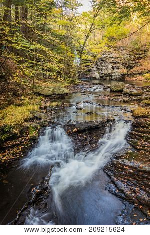 Waterfalls flow smoothly over rocks surrounded by fall foliage in Delaware Water Gap section of Pocono Mountains, PA