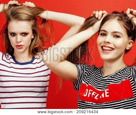 two best friends teenage girls together having fun, posing emotional on red background, besties happy smiling, lifestyle people concept
