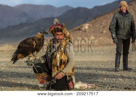 SAGSAY, MONGOLIA - SEP 28, 2017: Kazakh Eagle Hunter traditional clothing, while hunting to the hare holding a golden eagle on his arm in desert mountain of Western Mongolia.