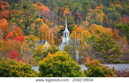 New England church covered with Fall foliage
