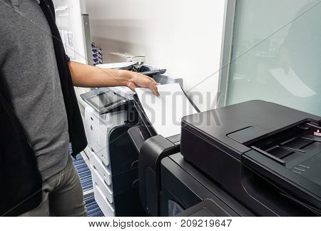 businessman put paper sheet into office printer tray for printing documents