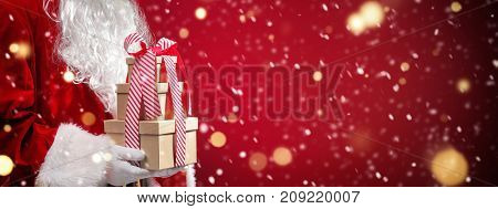 Santa Claus holding gift boxes with Christmas lights.