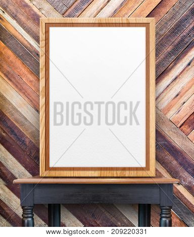 Blank wooden photo frame leaning at diagonal wood wall on vintage wood tableTemplate Mock up for add design or text.