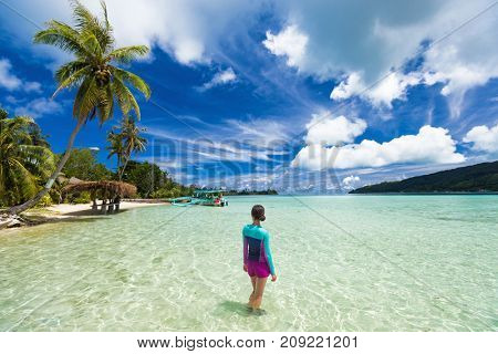 Beach vacation tourist woman swimming in French Polynesia island on cruise excursion at Huahine paradise motu. Tahiti travel holiday. Girl wearing sun protection clothing rashguard for solar skincare.