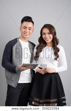 Couple With Digital Tablet And Credit Card In Studio Isolated Gray Background