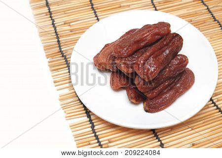 Natural Solar Dried Banana on dish isolated white background.