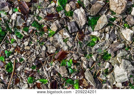 Shards of glass on shards of stone. Glass debris. Broken bottles. Background and texture