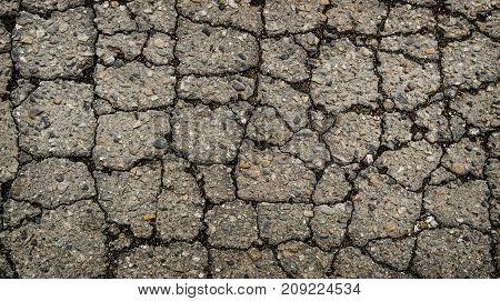 Old worn and cracked asphalt with cracks. Cracked asphalt background