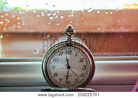 Old retro pocket watch at the window, closeup details photography