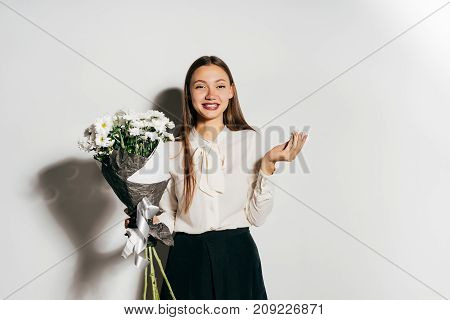 happy girl in blouse holding a bouquet of beautiful white flowers and looking directly at the camera, isolated on a white background. Happy birthday, fun.