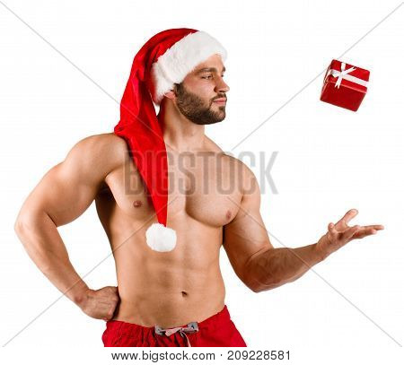 Torso fitness man dressed as Santa Claus with red hat and small gift box with white stripe, isolated over white background. Man flip up gift box in air. Strongman is looking at the gift box