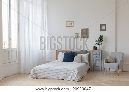 Interior of white and gray cozy bedroom with plants on the bedside table
