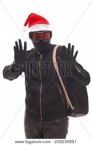 Masked burglar with santa claus cap holding his sack posing on isolated background