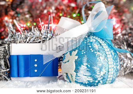 Christmas present and Christmas ball on snow against a background of shiny tinsel. glowing lights. bokeh. Christmas and New Year. place for text