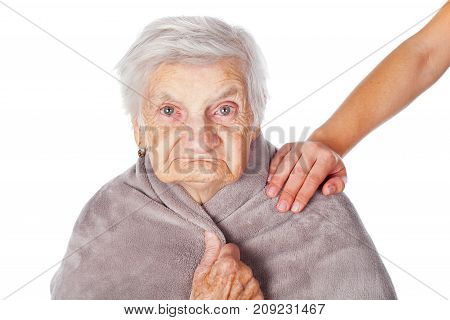 Senior ill woman on isolated covered by a warm blanket caregiver's helping hands