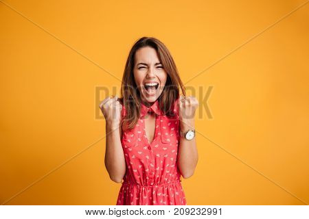 Close-up of emotional brunette woman keeping hands in fists, screaming while celebrating win, isolated on yellow background