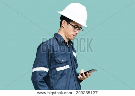 Asian manEngineer or Technician in white helmet glasses and blue working shirt suit using smart phone isolated on green mechanic and Oil and Gas industrial concept with clipping path.