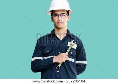 Asian manEngineer or Technician in white helmet glasses and blue working shirt suit holding wrench isolated on green mechanic and Oil and Gas industrial concept with clipping path.