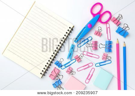 Stationary concept Flat Lay top view Photo of school supplies scissors pencils paper clipscalculatorsticky notestapler and notepad in pastel tone on white background with copy space flat lay design.