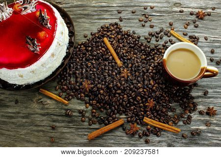 A cup of coffee with a big cake and coffee beans, anise and cinnamon on a wooden table. view from above