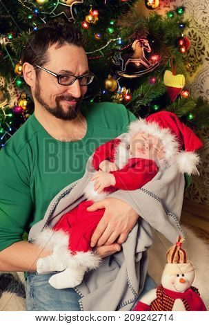 Beautiful baby Santa Claus sleeping on a father hands