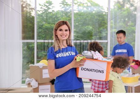 Woman holding box with donations. Volunteering abroad concept