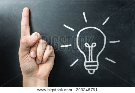 Getting new idea. Innovative, inspiring and creative learning and teaching. Teacher, educator, trainer or student pointing up with finger. Light bulb on chalkboard or blackboard.