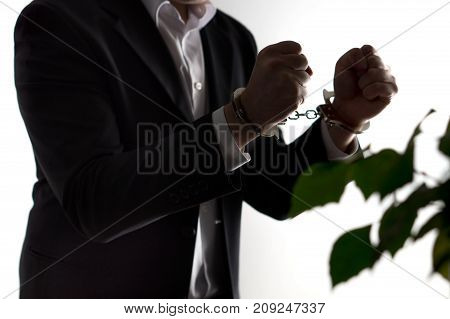 Financial fraud concept. Businessman, politician or man in a suit in handcuffs. Business criminal in shackles.
