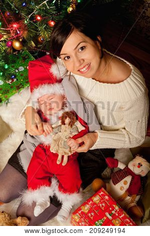 Newborn baby in Santa clothes sleeping on a mother hands near christmas tree