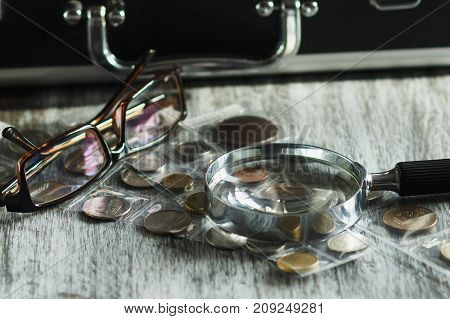 Coins, Magnifying Glass And Glasses