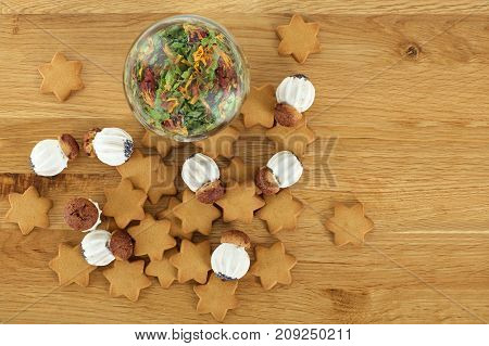 Delicious cookies and tea leaves in glass jar on brown wooden table