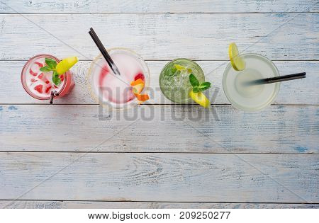 Colorful cocktails. Mojito, Red Cocktail with ice and lime, Margarita, Cosmopolitan on wooden table close up.