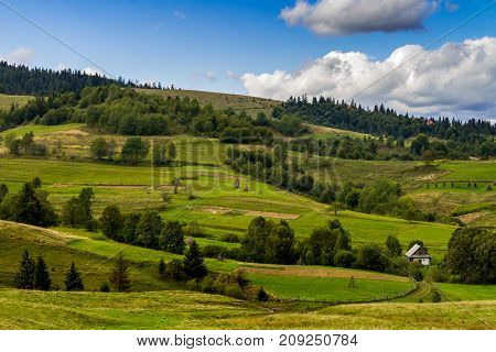 Rural house near the agricultural land in the Carpathian Mountains. Rural mountain landscape in the early autumn day.