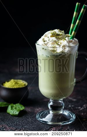 Green tea matcha latte in a glass cup on black background. Concept of a healthy diet, superfood, antioxidant, cleansing