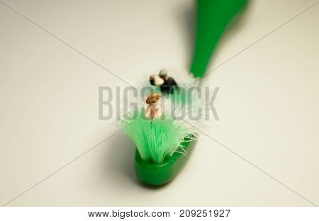 Miniature people: Miniature farmer is agricultural harvest on a toothbrush. Concept image.