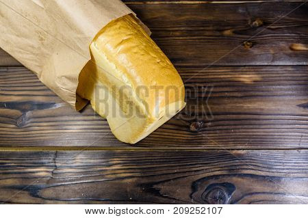 Loaf Of Bread In Paper Bag On Wooden Table. Top View