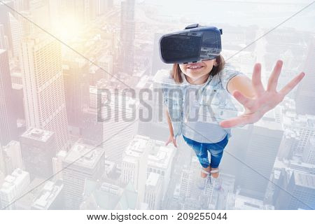 New sensation. Pleasant smiling girl in a VR headset raising her palm and spreading her fingers wide while being positioned against urban background