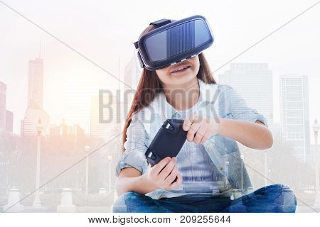 Having fun. Adorable little girl squatting cross-legged, wearing a VR headset and using a video game controller to play a game while being against an urban background
