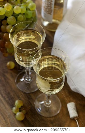 White Wine With Glass Goblets And Grape Bunches On A Wooden Background.