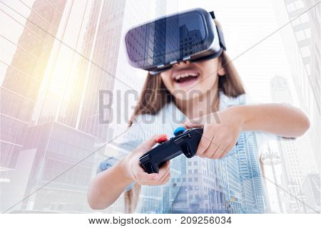 Keen on playing. Adorable little girl playing a video game, using a VR headset and a video game controller while her image being superimposed on the urban background